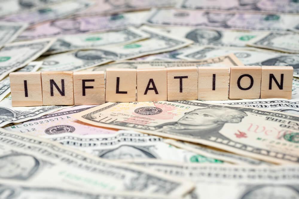 "Word ""Inflation"" in wooden block on US Dollar bills"